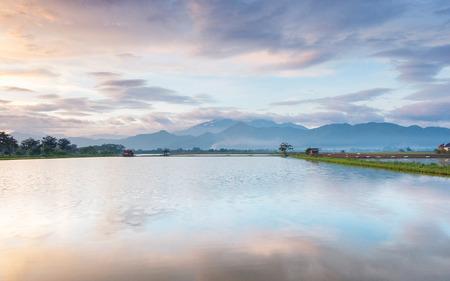 地平線に伸びる非常に広大な, 広範な, 大規模な, 広々 とした池の写真。それの後ろの丘や山行も広大な美しい雲紫空です。 写真素材