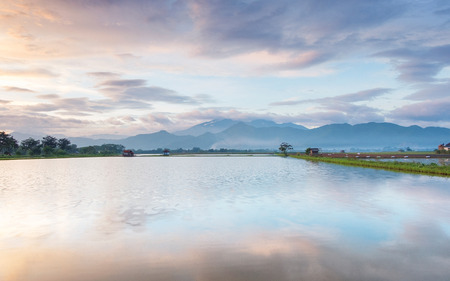 Photo of very vast, broad, large, spacious pond, stretched into the horizon. Behind it is a line of hills and mountains that also expansive, and beautiful cloud purple sky.