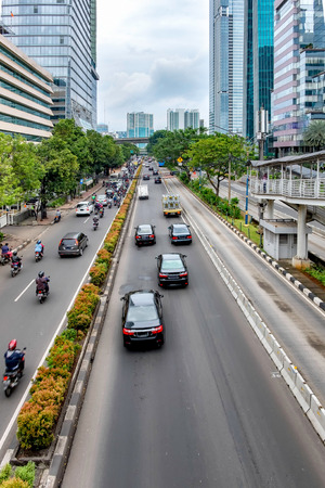 Photo of big road in Jakarta and its traffic, consist of car and motorcycle,  with skyscraper buildings in the both side of the road. Captured in Rasuna Said Street, Indonesia.