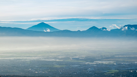 faraway: Aerial view of city and mountain when illuminated by sunlight in faraway, captured  from Moko Hills when weather is sunny, Bandung, Indonesia