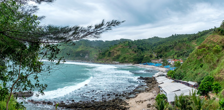faraway: Panorama photo of shore or beach with houses and traditional boat for fisherman in faraway, with waves broken forming white foam, captured from top. Captured on Menganti Beach, Kebumen, Indonesia