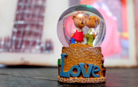 A glass toy representing a love. There is two character inside the glass, resembling a bear. With one of the character kissing other characters cheek.