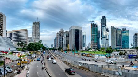 ジャカルタ、インドネシアの美しいスカイラインのパノラマ。近代的な超高層ビルと美しい空と白い雲で afternoom し、中等度のトラフィックの大きな