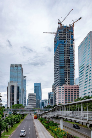 buildingsite: Photo of skyscrapper building under construction, with scenery of empty traffic and other skyscraper buildings. Captured in Jakarta, Indonesia