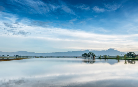 Photo of very vast, broad, large, spacious pond, stretched into the horizon. Behind it is a line of hills and mountains that also expansive, and beautiful cloud and blue sky. This photo captured after sunrise, captured in Bandung, Indonesia Stock Photo