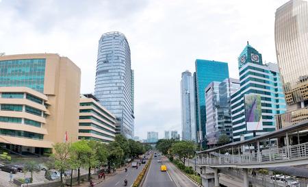 ジャカルタとそのトラフィックの道の道路の両側に超高層ビルのパノラマ写真。ラスナと述べた通り、インドネシアで捕獲。