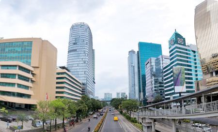 Panorama photo of big road in Jakarta and its traffic, with skyscraper buildings in the both side of the road. Captured in Rasuna Said Street, Indonesia.