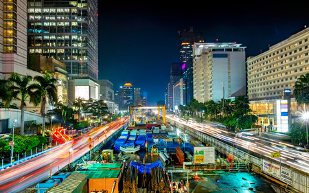 Monorail or mass rapid transit construction at night, in M.H Thamrin Street, Jakarta. Showing beautiful buildings and light trail from busy traffic.  Urban Skyline, Building Exterior, Capital Cities