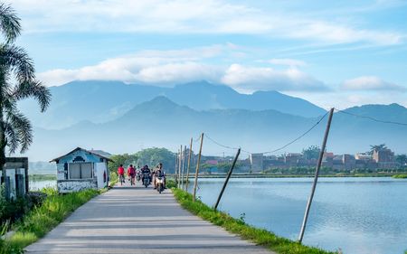Beautiful little street in rural area, with house and pond in the side of the road, huge line of mountains in the background and with people crossing this street using motorcycle