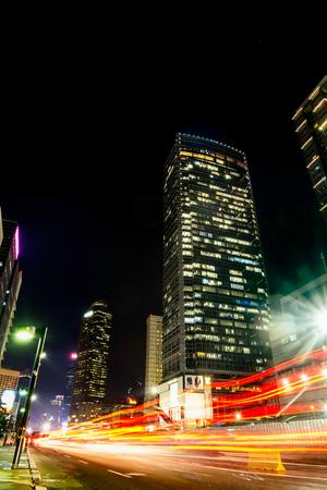 ジャカルタの skyscrapper の前にビジー状態のトラフィックの光跡。 都市の地平線、建物外観、首都