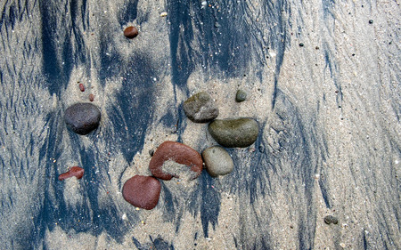 Beautiful formation of red, black and green rock on black and brown sand, captured on the beach. Captured on Menganti Beach, Kebumen, Indonesia
