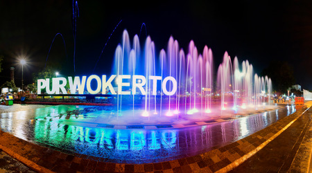 Iconic symbol of Purwokerto city, with neon glow behind colorful water fountain at night. Captured in Purwokertos city square, Banyumas, Indonesia