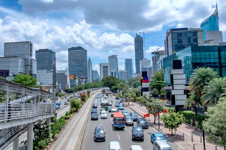 ジャカルタ、インドネシアの美しいスカイライン。中等度のトラフィックの午後、大きな道路でモダンな超高層ビルと美しい青い空と白い雲を示し