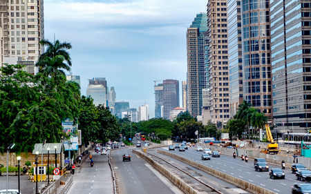 ジャカルタ、インドネシアの美しいスカイライン。中等度のトラフィックの午後、大きな道路でモダンな超高層ビルと美しい空と白い雲を示します 報道画像