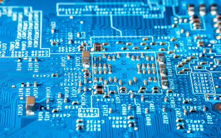 Photo of  electric component in electronic device, contain small resistor in beautiful rectangle formation, small capacitor, microchip and capacitor on blue printed circuit board. Look like a small city, captured using focus stacking method Stock Photo