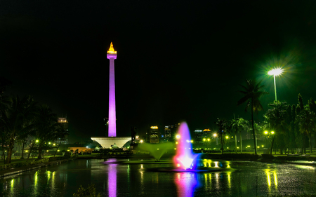 National Monument (Monas) at night, in front of big pool and colorful water fountain, create beautiful reflection of this monument., this is one of iconic monument in Jakarta, Indonesia