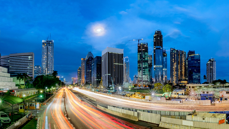Panorama of iconic skyline  light trail of  and heavy traffic in Sudirman Street, Jakarta, Indonesia at dusk, showing light trail  of busy traffic and iconic skyscrapers in Jakarta, iluminated by moon light.  Urban Skyline, Building Exterior, Capital Citi