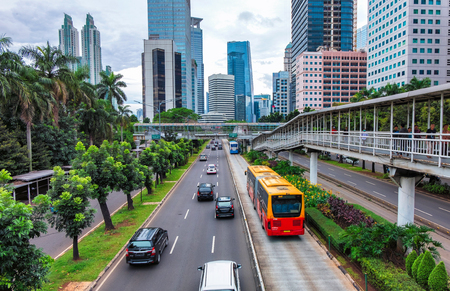Red colored public transport bus on the road,  on the way to next bus stop, in busy street at Jakarta, Indonesia. With group of skyscraper buildings in the background.