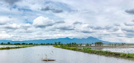 地平線に伸びる非常に広大な, 広範な, 大規模な, 広々 とした池の写真。それの後ろの丘や山行を黄色も広大な美しい雲空です。この写真はインドネ