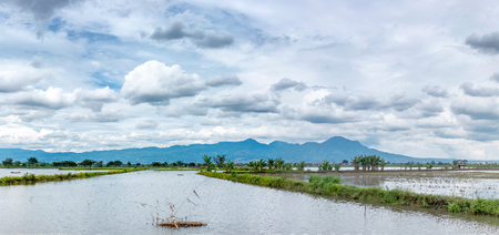 Photo of very vast, broad, large, spacious pond, stretched into the horizon. Behind it is a line of hills and mountains that also expansive, and beautiful cloud yellow sky. This photo captured at afternoon, captured in Bandung, Indonesia
