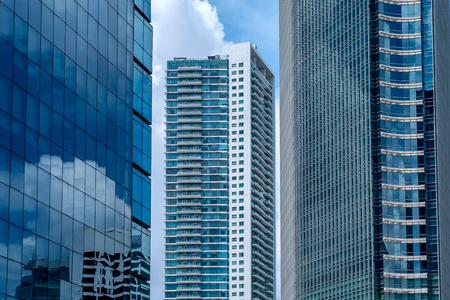 建物のもう一つのビルの間に高層ビルも高層ビル、空の反射を示すと、インドネシアのジャカルタで建物のガラス窓を表示します。