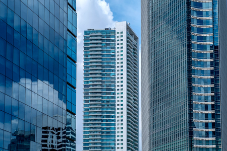 Skyscraper building in between another buildings, also show glass window on skyscraper, showing reflection of sky and building in Jakarta, Indonesia Standard-Bild