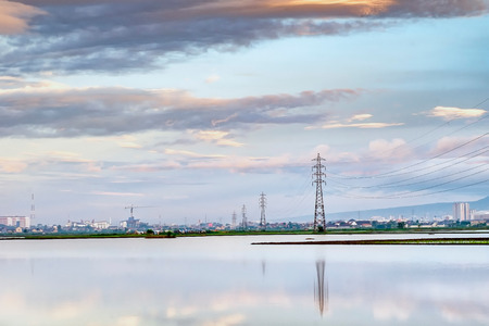 Transmission tower, electricity pylon or a power pylon, standing majestically lined up to the horizon, in front of large lake or pond, also with beautiful cloud and city in the background, captured at sunrise Stock Photo