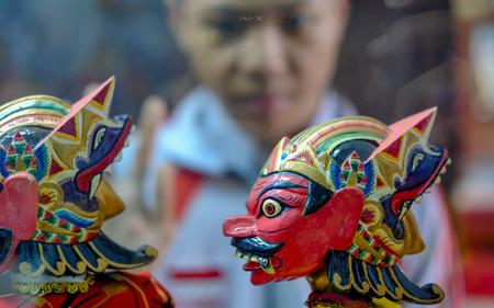 インドネシア ・西ジャワ島から木製の人形の頭。赤い顔と怖い見て、反対側から人形を表示する一方の少年。