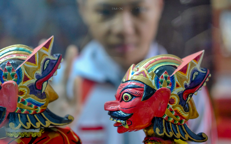 Head of wooden puppet from west java, Indonesia. With red face and scary look, meanwhile a boy viewing the puppet from other side.