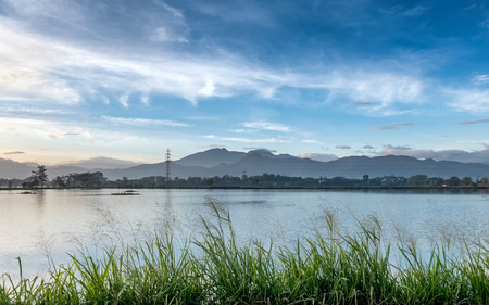 Huge and expansive pond or lake, behind green weeds. With beautiful line of mountain or hill, transmission tower and beautiful blue sky and white cloud, captured after sunrise, in Bandung, Indonesia