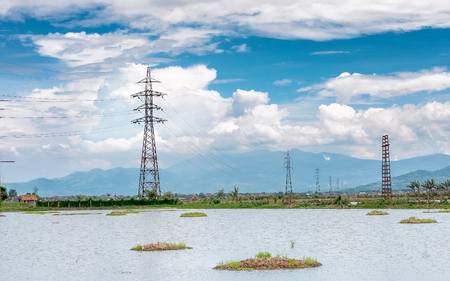 Transmission tower, electricity pylon or a power pylon, standing majestically lined up to the horizon, in front of large lake or pond, also with beautiful cloud and mountain in the background, captured at daytime or noon