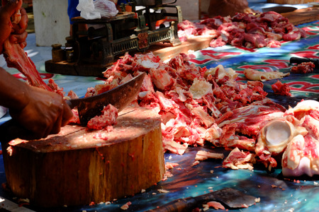 Pile of chunks raw cows meat and bone, and also people who chopping meat using  machete or chopping knive