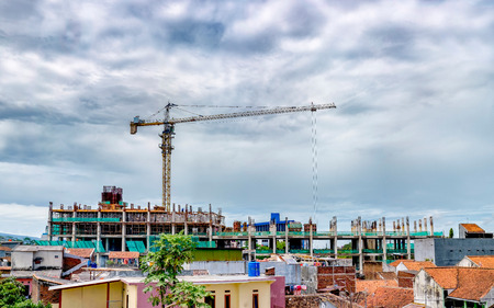 Large crane at work, in building construction site, in front of beautiful cloudy sky, and in urban environment