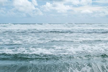 波ビーチの別の波をクラッシュしてカメラマンに向かって。 地平線の美しい雲。Menganti ビーチ、Kebumen、インドネシアでキャプチャ