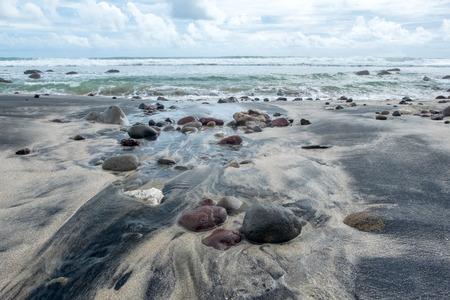小さな岩やビーチ波によって掃引された後に黒い砂浜の形成。Menganti ビーチ、Kebumen、インドネシアでキャプチャ