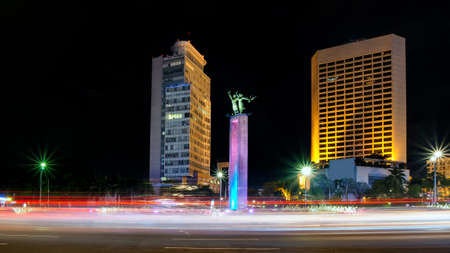 Selamat Datang monument in front of Jakarta's skyscrapers. Behind busy traffic in Bundaran Hotel Indonesia, or Hotel Indonesia roundabout, Sudirman Street,  Jakarta. Urban Skyline, Building Exterior, Capital Cities