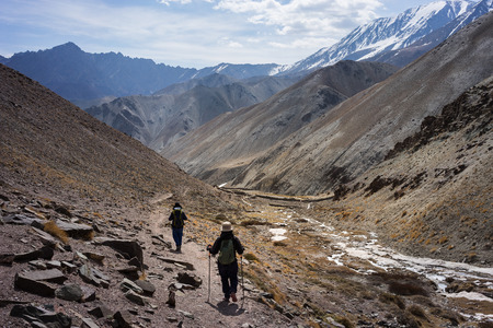 A man and a woman trekking on Markha valley trekking route - Leh Ladakh - India 免版税图像