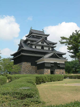 Landscape view of the main tower of Matsue Castle during the daytime with hedges from the castle gardens in the foreground and blue sky in the background           Editöryel