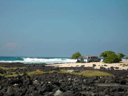An SUV parked and people camping on the volcanic shore of the Big Island of Hawaii.