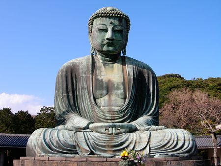The famous Kamakura Daibutsu (Giant Buddha) statue in Japan, with a bright blue sky in the background photo