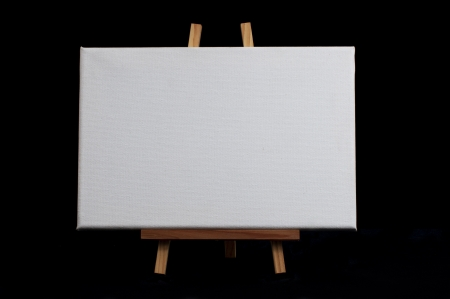 Easel with blank canvas isolated on black background photo