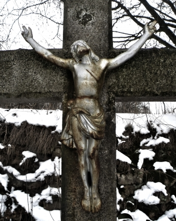 Detail of Jesus Christ on cross in winter time. Statue. photo