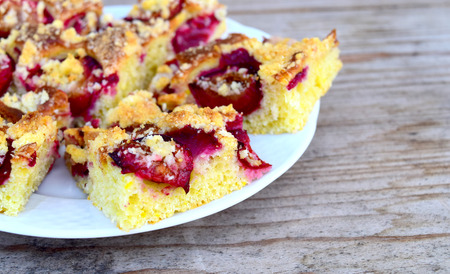 Sweet plum cake or dessert on white plate and wooden table. Food theme. photo