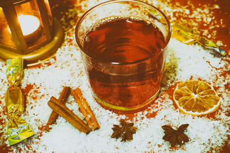 christmas motive: Winter hot drink punch with few ingredients - cinnamon, badyan, fruit. Snow christmas holiday background. Retro vintage motive.