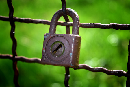 Detail of an old lock pendulous on old iron fence with green color on background.