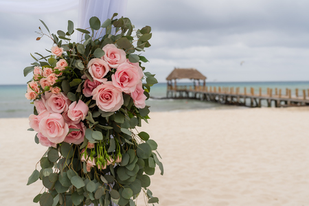 Romantic decoration with roses of a beach wedding on the beach with sea in the background Stok Fotoğraf