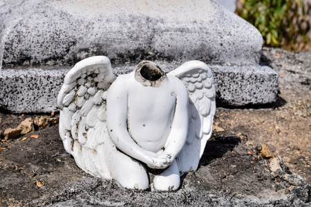 Angel statue without a head on a cemetery