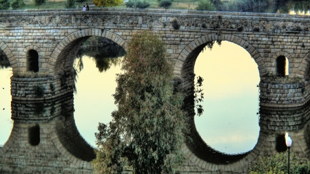 1st century: Roman bridge (1st century BC) and reflections over the Guadiana river (Spain) Stock Photo