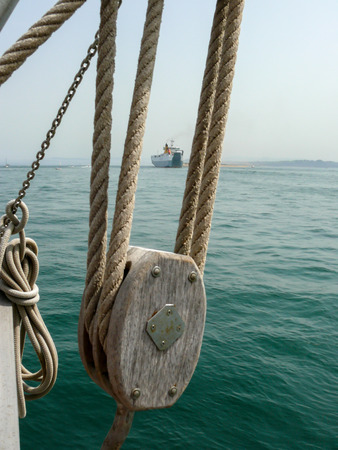 schooner: Close-up of pulley and hoist of a schooner with a merchant ship in the background