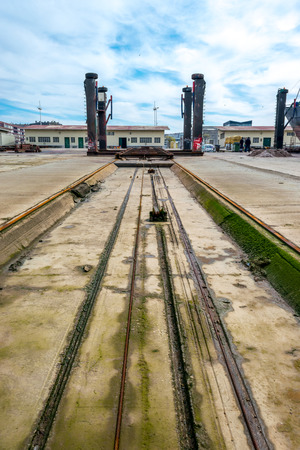 drydock: Perspective of machinery and a shipyard ramp